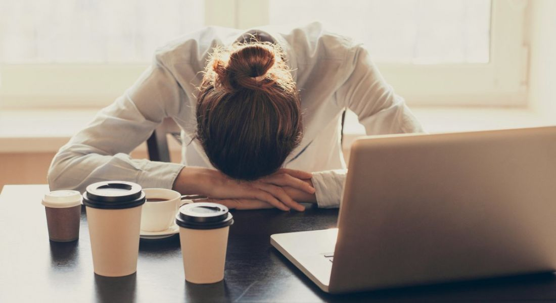 A woman with her head resting on her arms beside a laptop and several coffee cups. She is clearly unhappy at work.