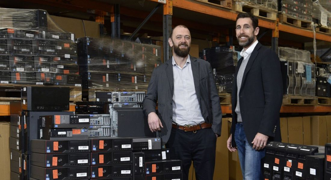 Two bearded men in sports jackets standing in a room full of IT equipment.