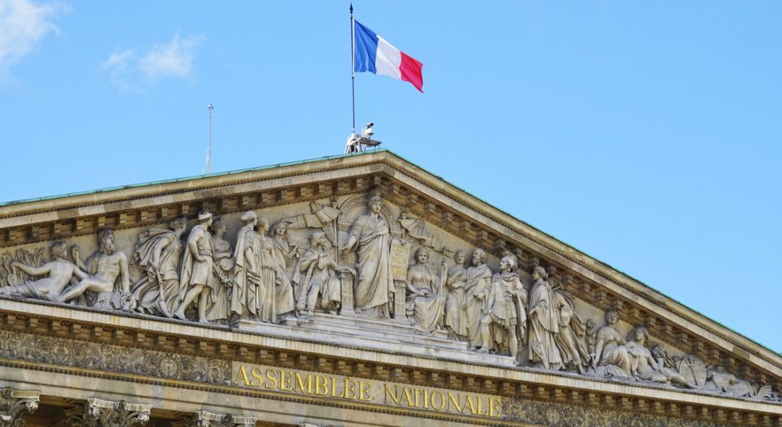 A view of an ornate government building In France with a French flag flying overhead against a clear sky.