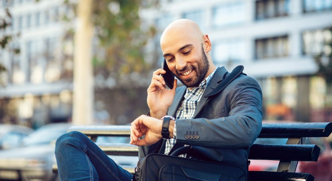 A young businessman sitting on a park bench n a metropolitan area looking at his watch and smiling.