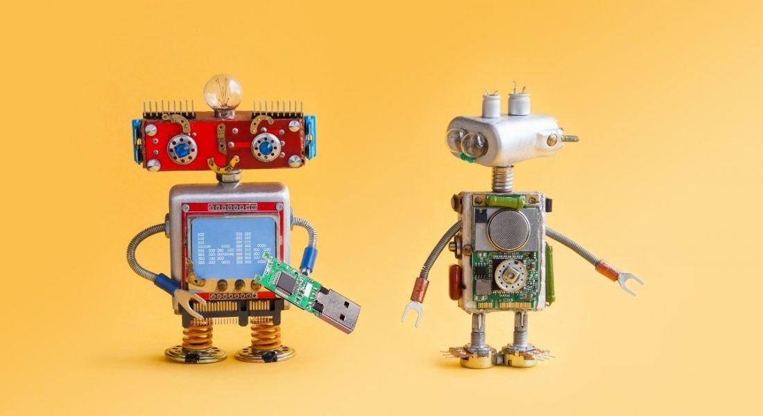 Two toy robots against a bright yellow background.