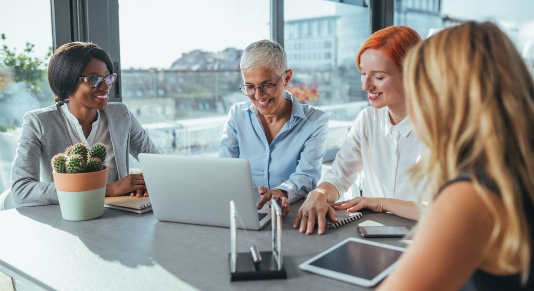 Four women of different ages work together on devices and notebooks in a meeting room overlooking a cityscape.