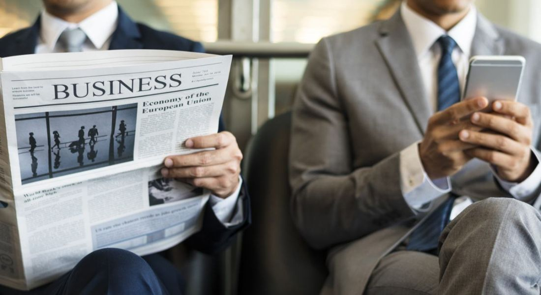 Two men in suits, the one on the left reading the business section and the one on the right using his phone.
