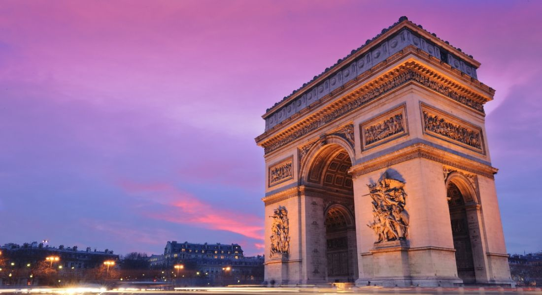 A view of the Arc de Triomphe in Paris against a purple twilight, illuminated by street lights.