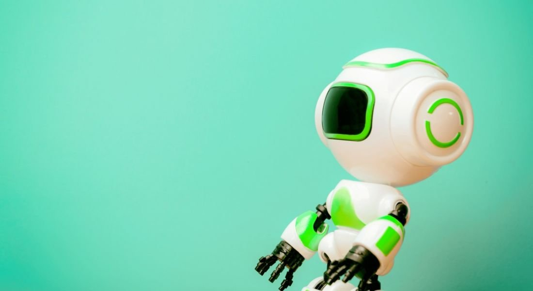 A toy robot with illuminated green panels standing against a mint green background.