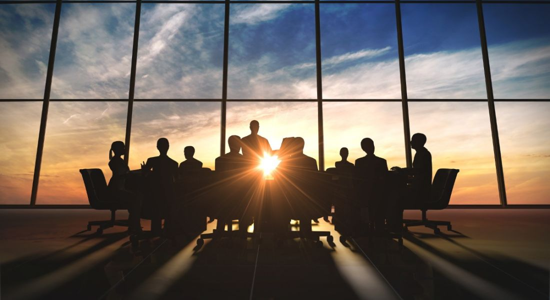 Silhouette of a team of people at a meeting in a room with wall-to-ceiling glass through which the sunrise is streaming in.