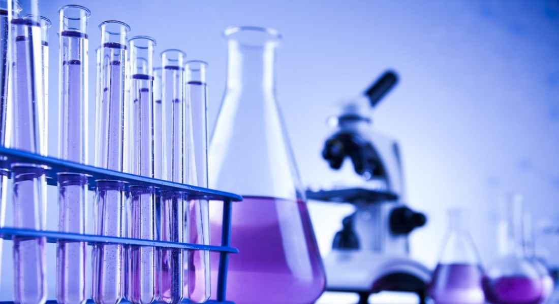 A purple gradient over a view of a laboratory with beakers, a microscope and a rack of test tubes sitting on a table.