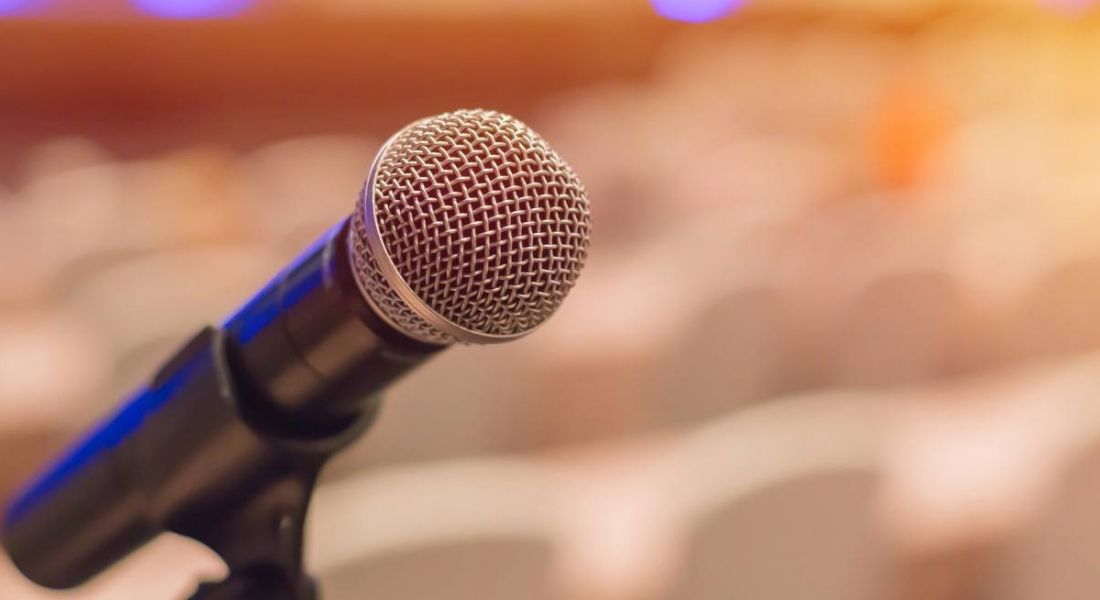 View of a microphone on a stand with a blurred out conference room in the background.