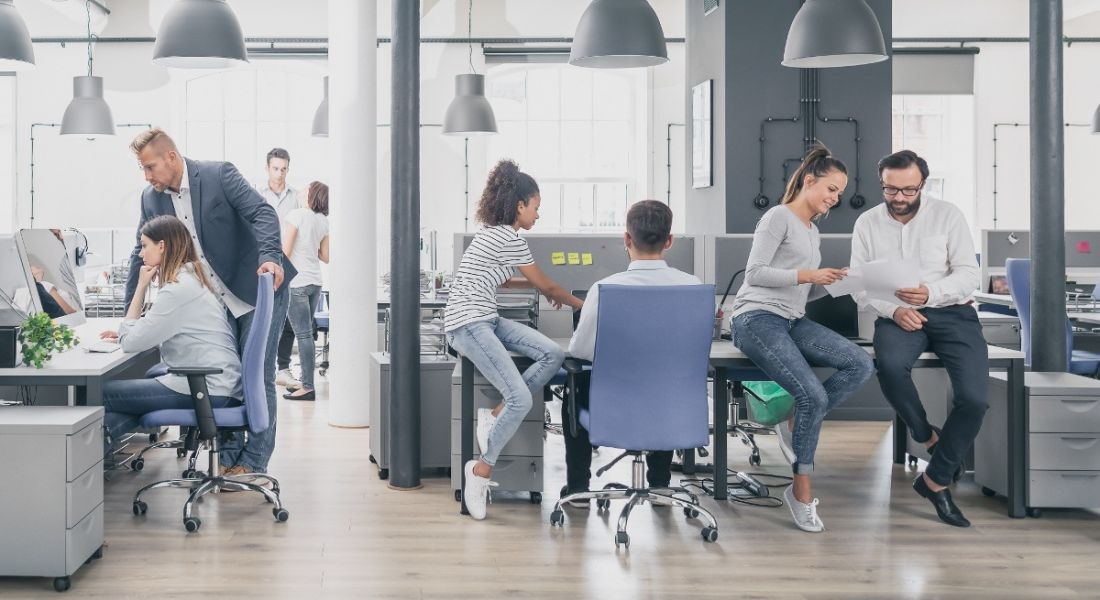A group of diverse people in an office working and communicating in various ways, representing internal communications.