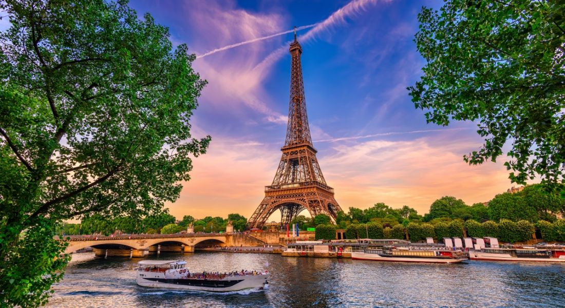 view of golden Eiffel Tower against purple sunset backdrop, with green trees and canal boats in foreground.