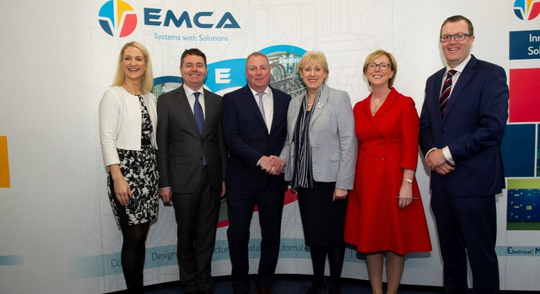 Three men and three women stand side by side in front of an EMCA sign.