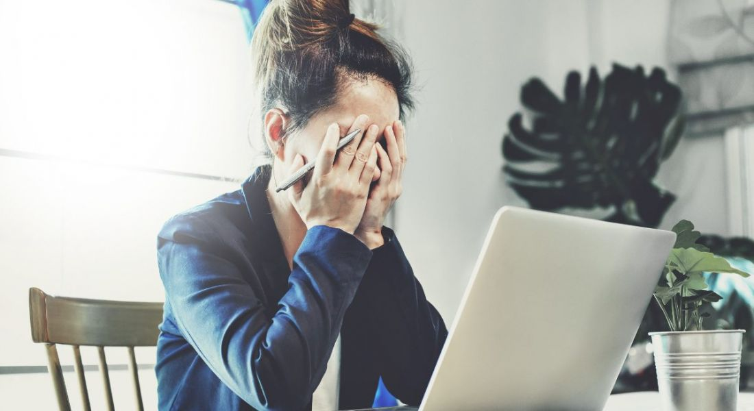 A stressed-out business woman with her head in her hands in front of a laptop, doing low-paid work.