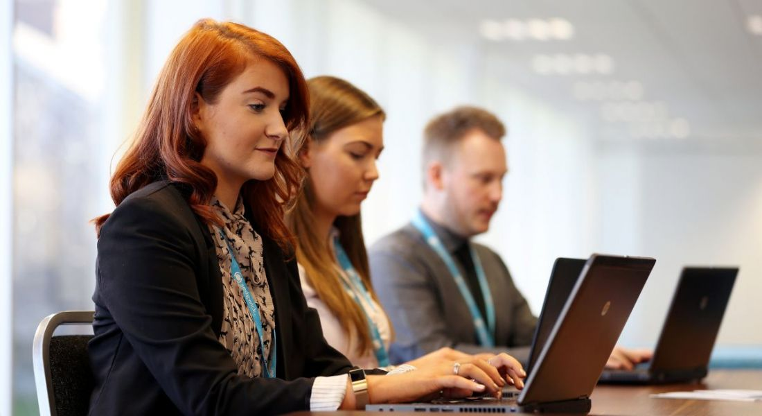 A red-haired woman working on a laptop in the foreground with two other employees working beside her at Sedgwick.