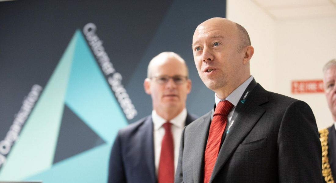 A bald man in a suit speaking in front of another man. He is the CEO of Version 1, speaking at an office opening.