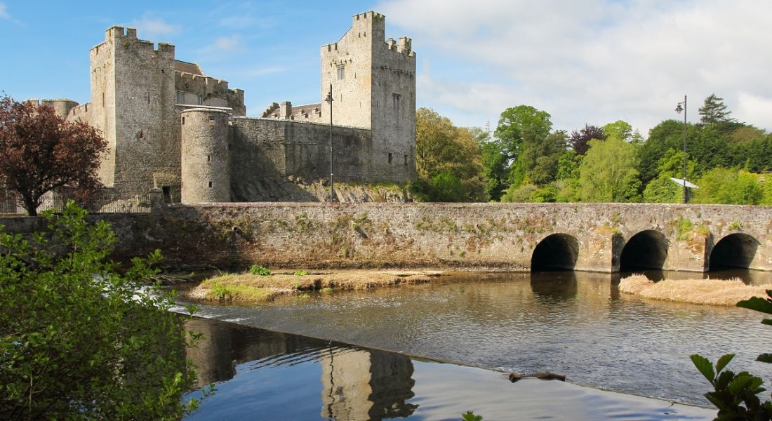 Grey stone castle of Cahir in Tipperary reflected in water under bridge in foreground.