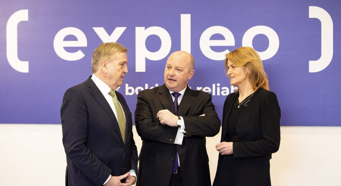 Formally dressed middle-aged men and woman standing in front of a purple wall with an Expleo logo.