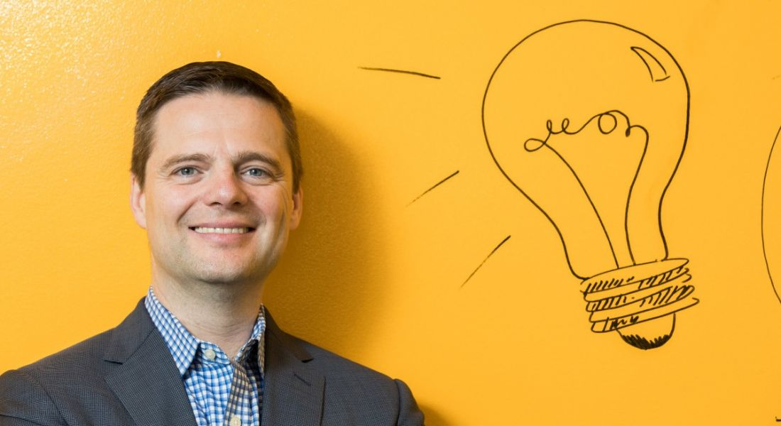 A man in a grey suit and checked shirt smiling at the camera against a canary yellow wall with a lightbulb motif.