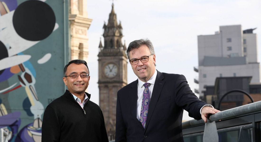 Two men, one in a black sweater and glasses and the other in a suit and glasses, stand against the backdrop of a clock tower looking at the camera.