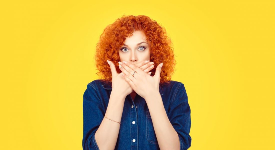 Against a bright yellow background, a woman with curly red hair wearing a denim shirt covers her mouth with her hands.