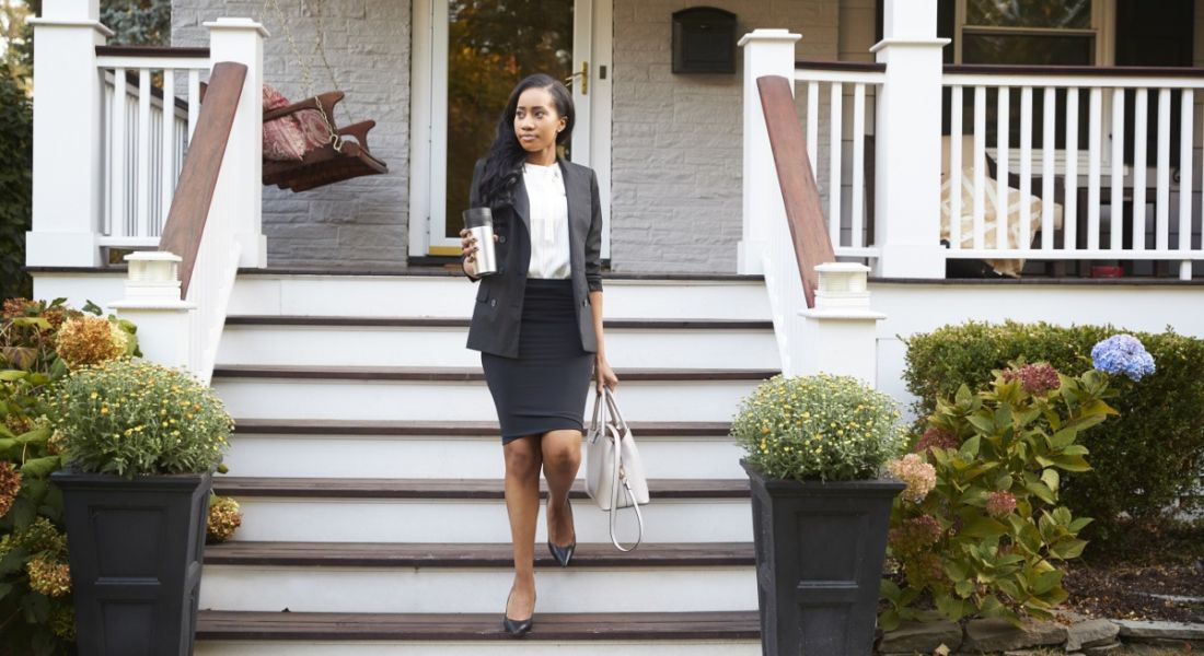 Woman in a dark business suit leaving her house to go do some unpaid work.