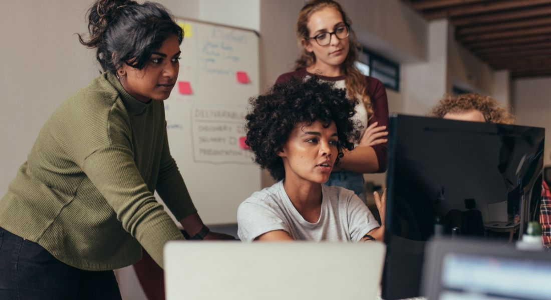 A group of women in an office gathered around a computer screen discussing work.