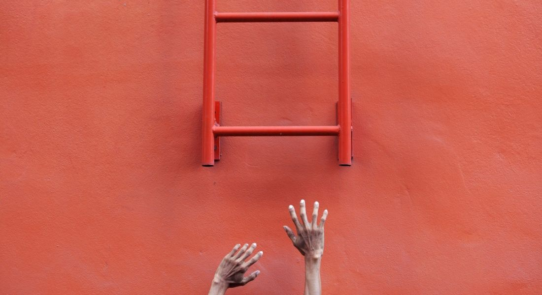 A red ladder attached to a wall symbolising career progression. The ladder ends half way down and two hands are trying to reach it.