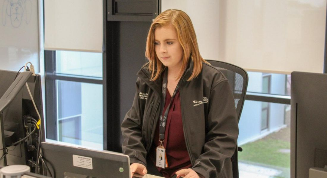 A red-haired young woman in a Jaguar Land Rover jacket working at a laptop.