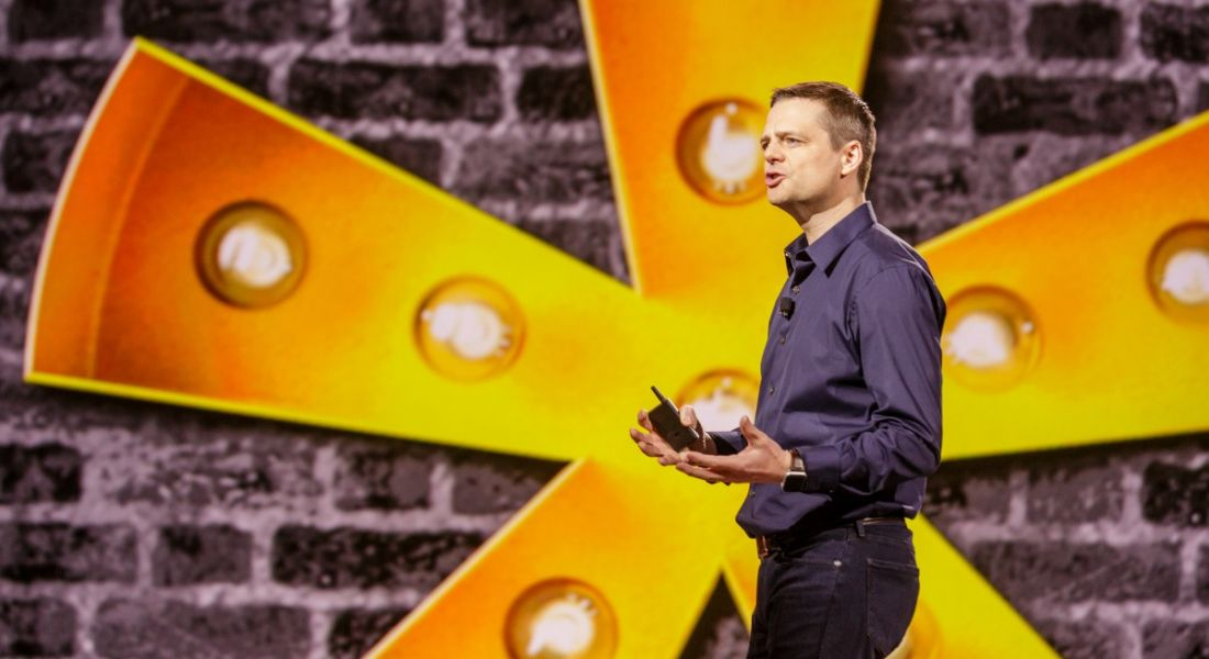 A man wearing a shirt and jeans speaking on stage with a yellow asterisk symbol behind him. It's Eric Mosley from Workhuman.