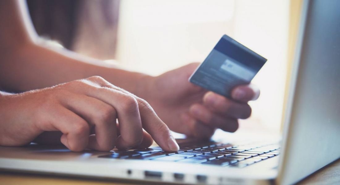 A close-up of a person on a laptop holding a credit card, representing fintech.