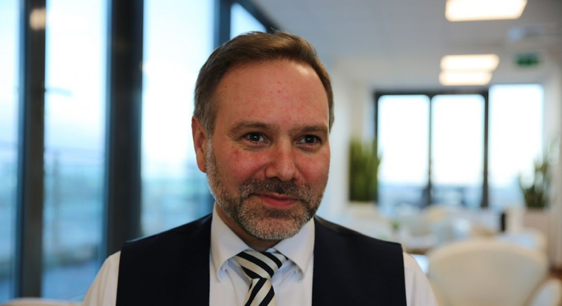A close-up of a man in a white shirt and black vest with a tie. He is director in SAP at the consulting practice at Deloitte.
