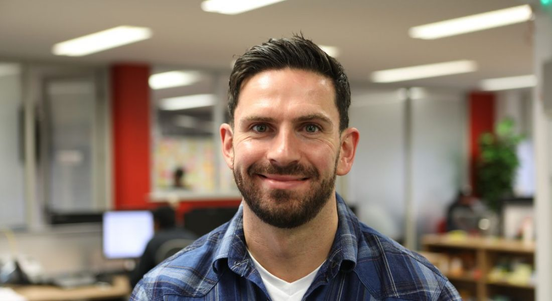 A young dark-haired man in a flannel shirt looks directly at the camera and smiles widely, showing dimples.