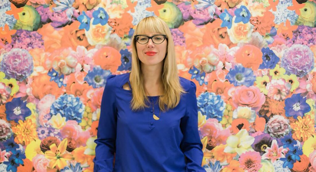 A blonde woman with glasses wearing a blue top standing in front of a floral backdrop. She is Jennifer Romolini.