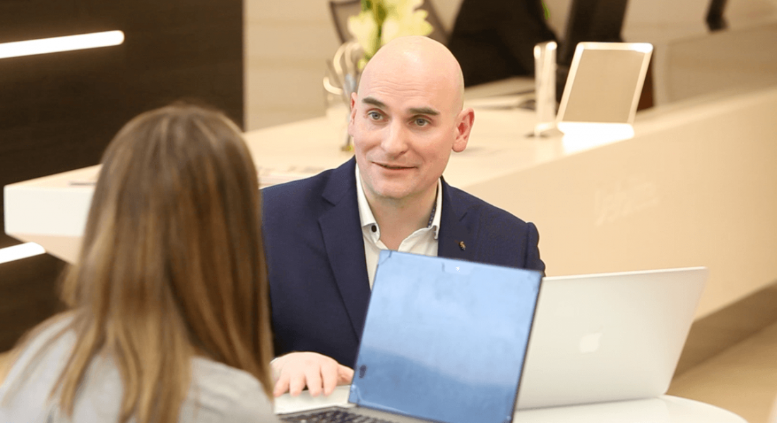 A bald man in a suit sitting with a laptop and talking to a brown-haired woman. They are representing agile working in Deloitte.