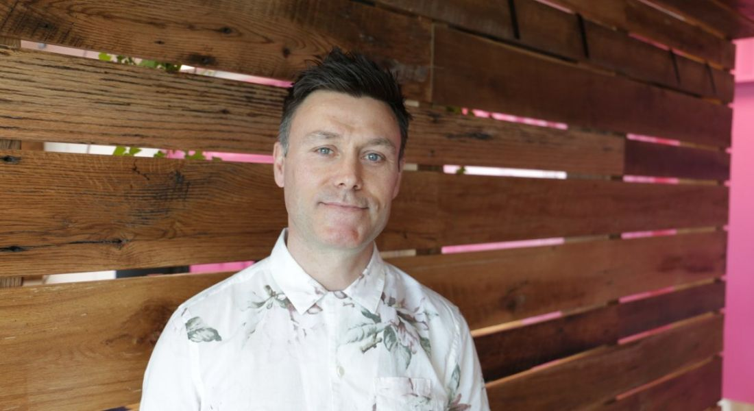 A headshot of a man with dark hair and short-sleeved white floral shirt. He works in UX design in Accenture.