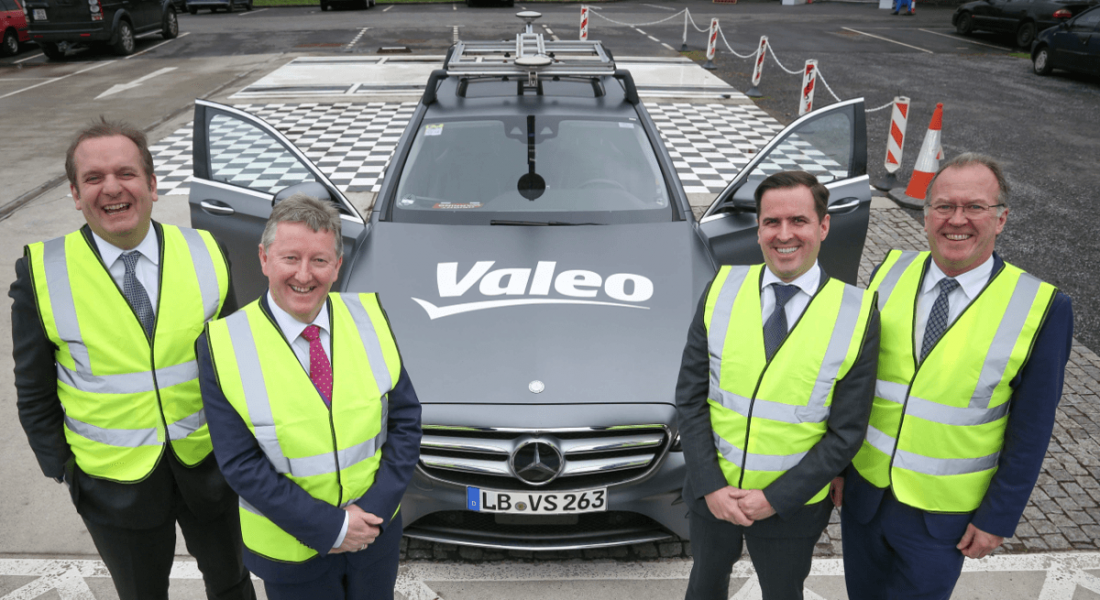 Four men in hi-vis jackets stand in front of an autonomous vehicle with sensors and the writing Valeo on bonnet.