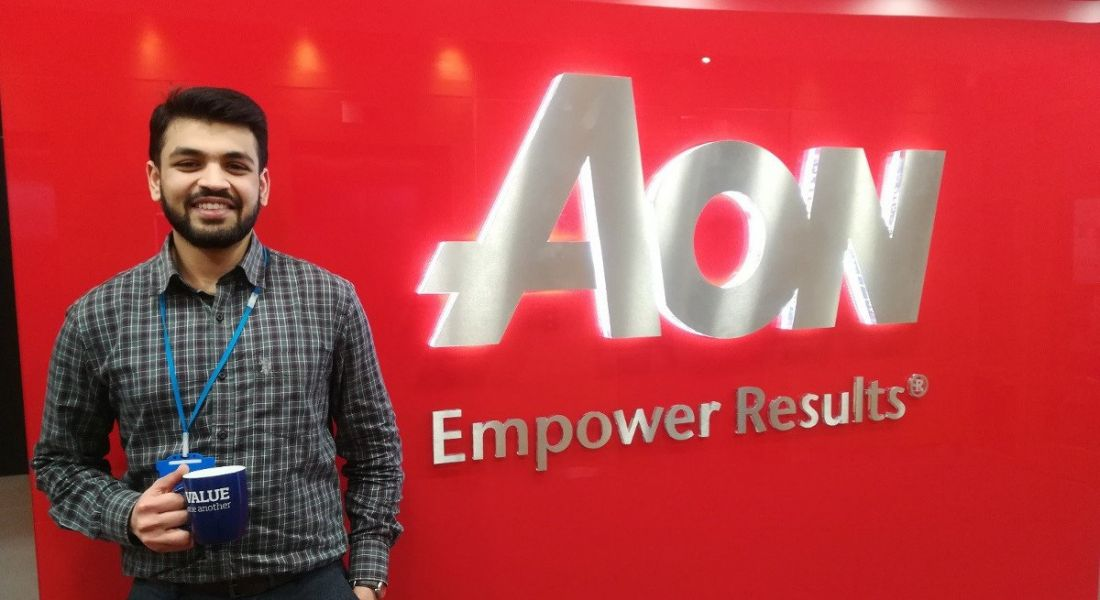 Image of a young man smiling while holding a coffee cup in front of an Aon logo.