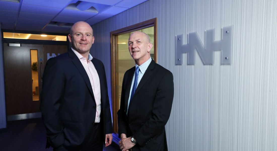 Two middle aged men in dark, crisply pressed suits standing next to each other smiling at the camera with HNH logo in background.