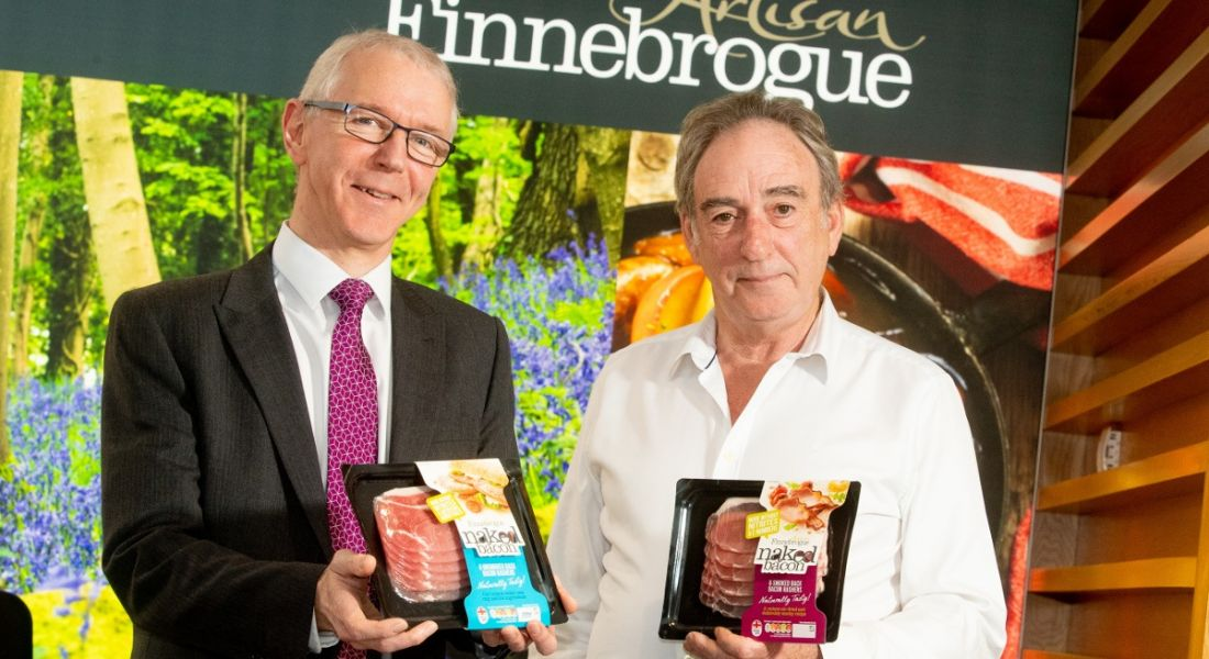 Two men standing beside each other in front of a Finnebrogue sign, each holding a packet of a product called Naked Bacon.