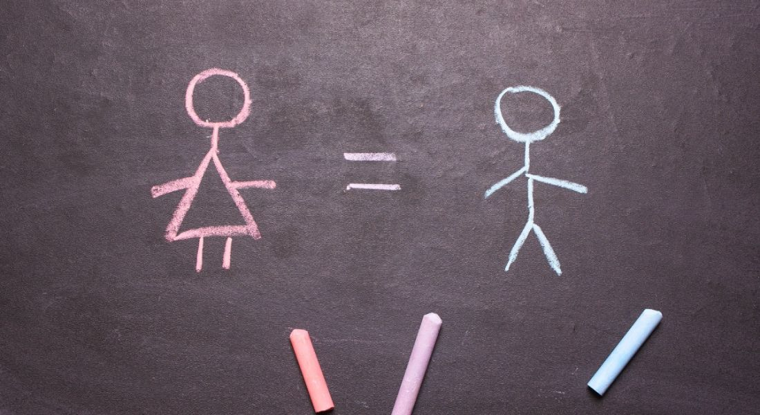 A chalkboard with a pink chalk stick woman with an equals sign beside a blue chalk stick man, showing gender balance.