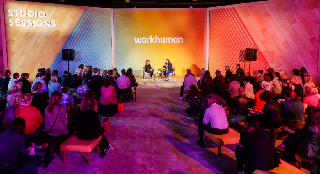 A shot of a small stage with the two women sitting in front of an audience. The Workhuman logo is behind them.