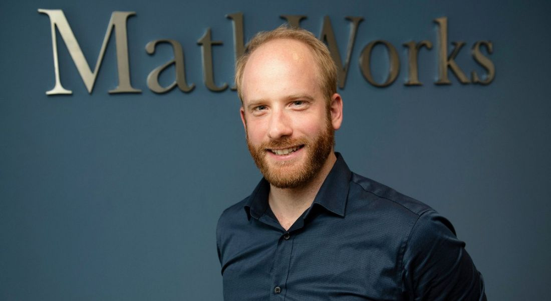 A professional man is smiling into the camera against a navy office wall with a sign reading 'MathWorks'.