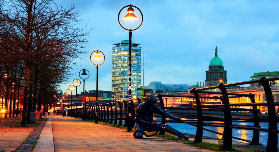 View of Dublin city illuminated at night with brass statue depicting man pulling in fish net near barrier.