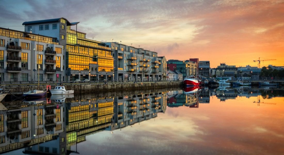 View of buildings with glass facades in Galway dock at sunrise.