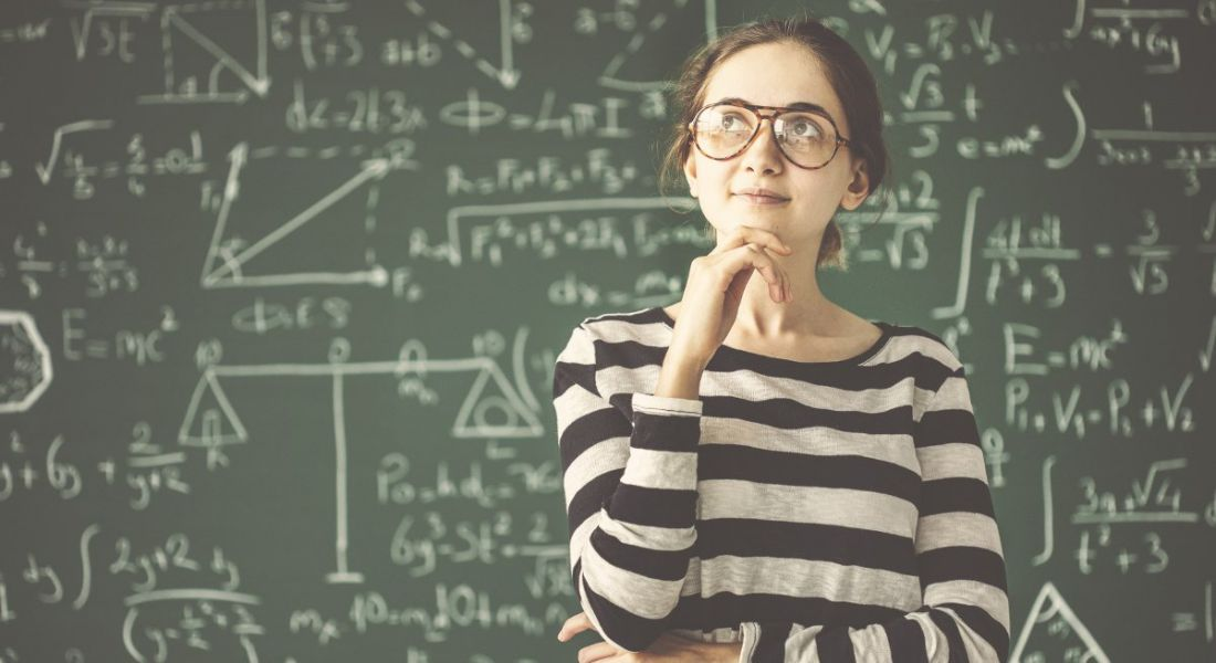 Young girl with glasses in a thoughtful position in front of a blackboard covered with maths equations