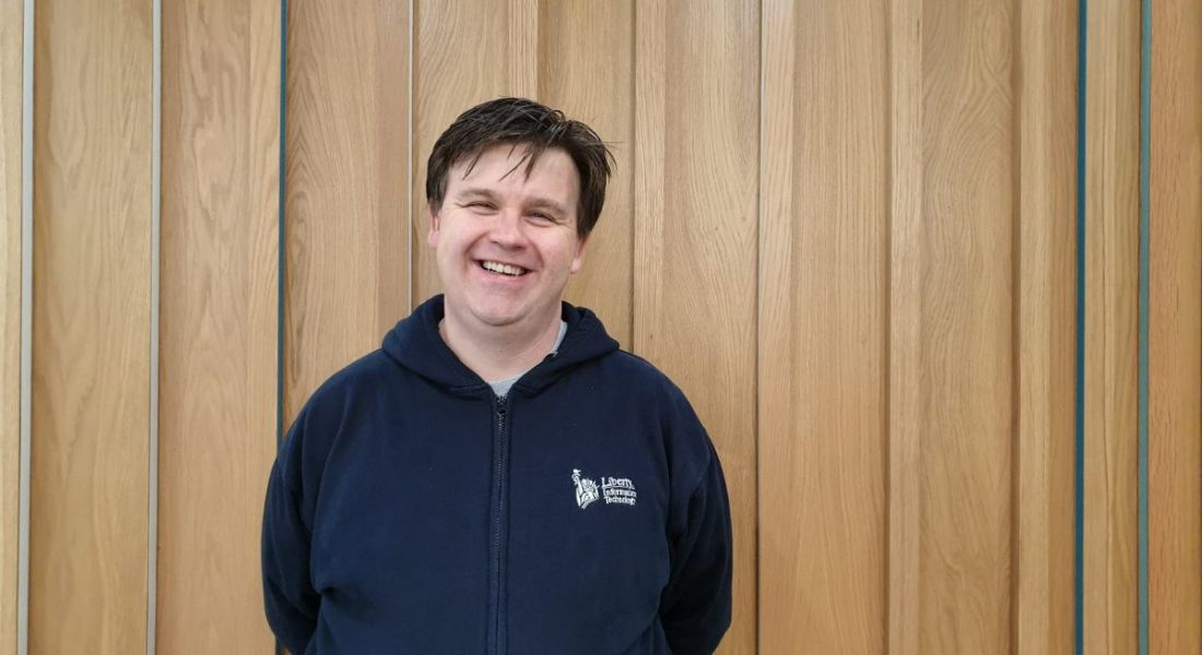 A man in a dark blue hoodie is standing against a wood-panelled wall and smiling into the camera.