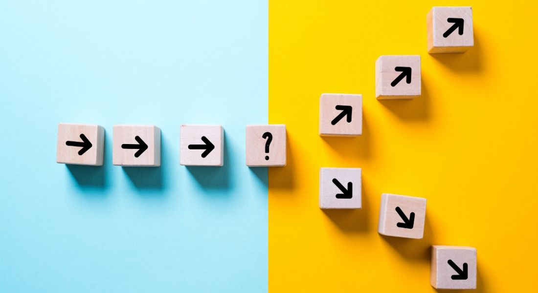 Blue and yellow background with small wooden blocks with arrows drawn on, leading to a question mark block and, from there, splitting into two paths.