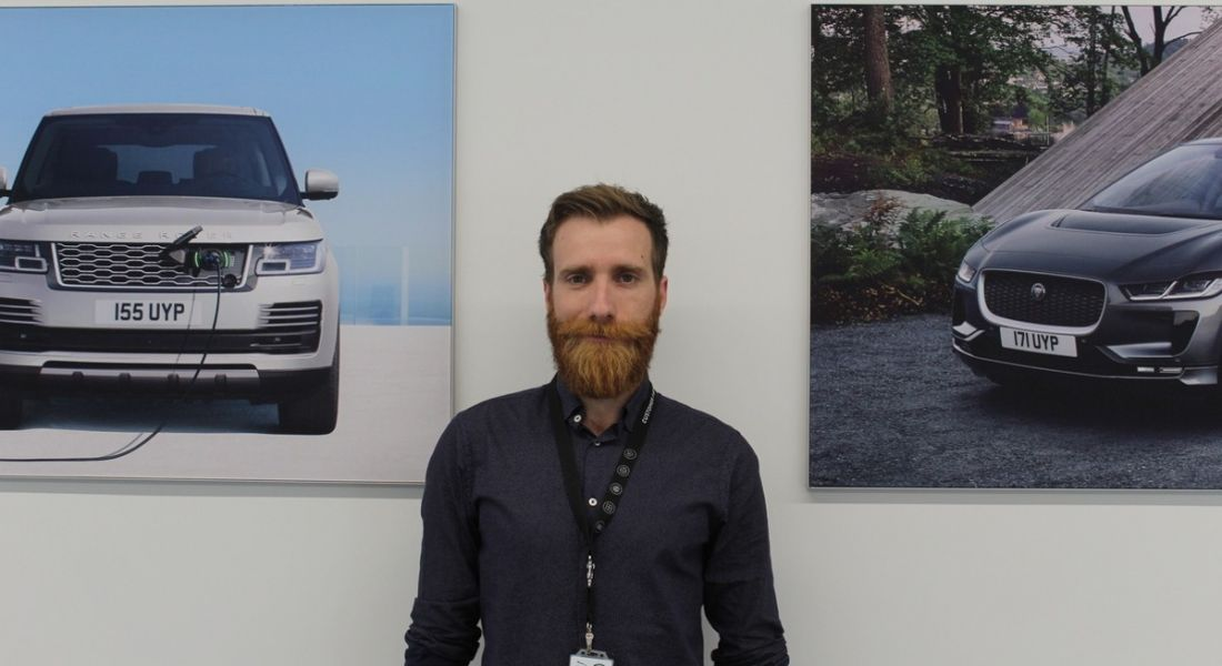 A male professional is standing against a white wall with photos of cars on either side of him, looking into the camera.