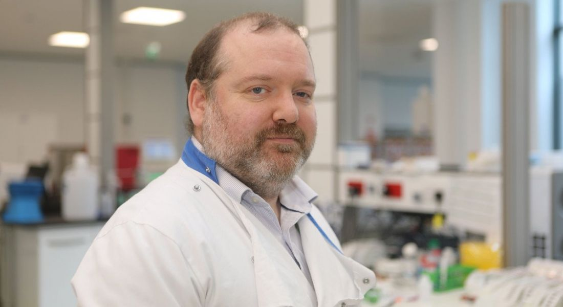 A man in a lab setting wearing a labcoat is looking into the camera.