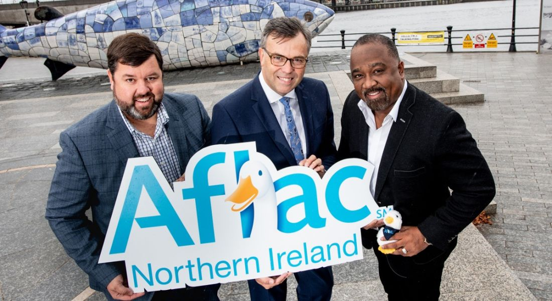 three businessmen holding an Aflac sign with a goose on it in an outdoors setting in Northern Ireland