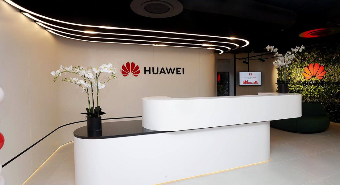 View of lobby of modern white offices with Huawei red lotus logo and the name Huawei written on wall.